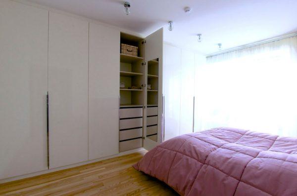 Miegamojo didelė balta spinta su varstomomis durimis.
