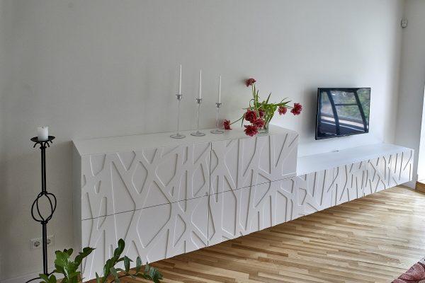 Stilinga balta pakabinama komoda, virš kurios tvirtinamas televizorius.