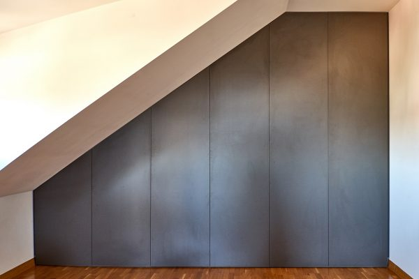 Montuojama mansardinė spinta su varstomomis durimis nuo sienos iki sienos, nuo grindų iki lubų.