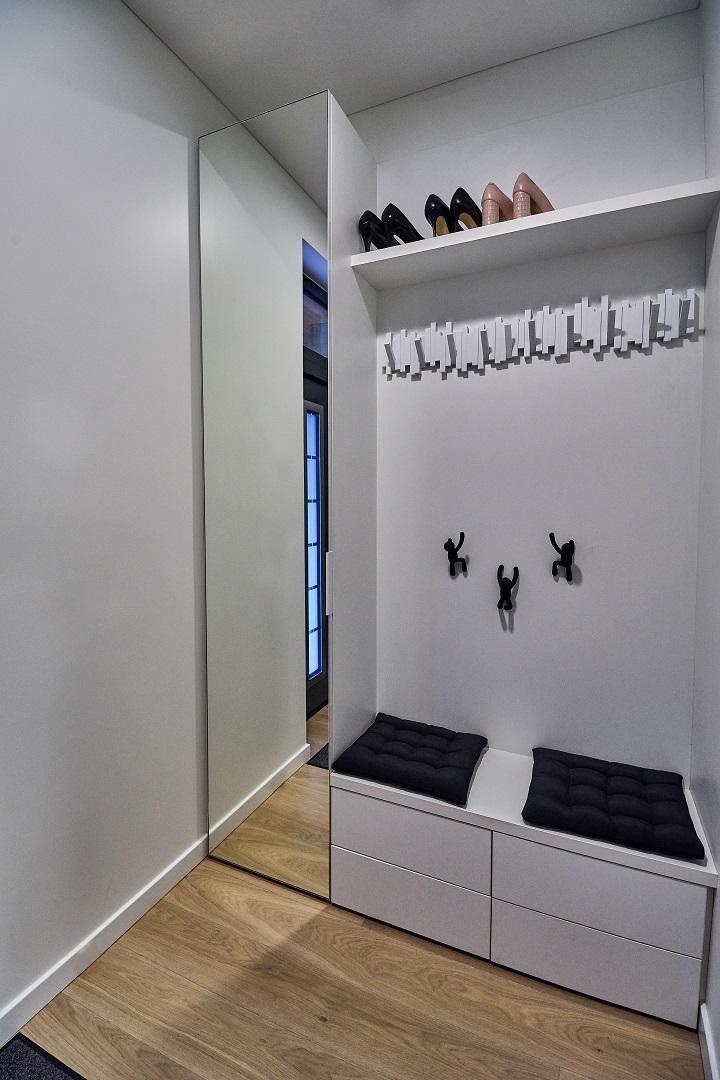 Holo baldus sudaro aukšta spintelė su veidrodžiu, žema spintelė batams ir ilga lentyna kepurėms. Baltą spalvą paryškina juodos pagalvėlės ir originalios pakabėlės.