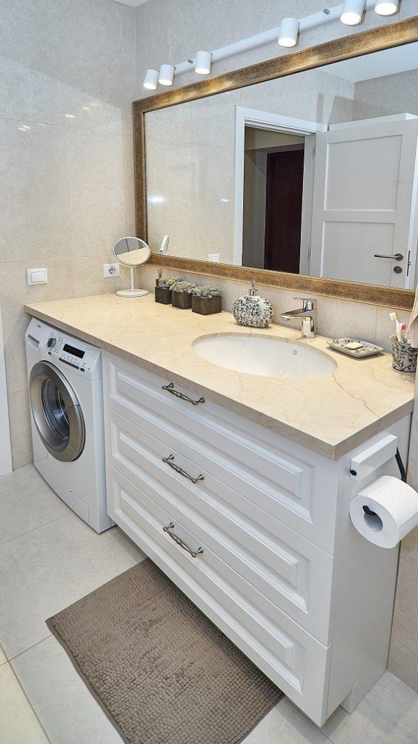 Prabangus lieto akmens stalviršis puošia vonios spintelę.