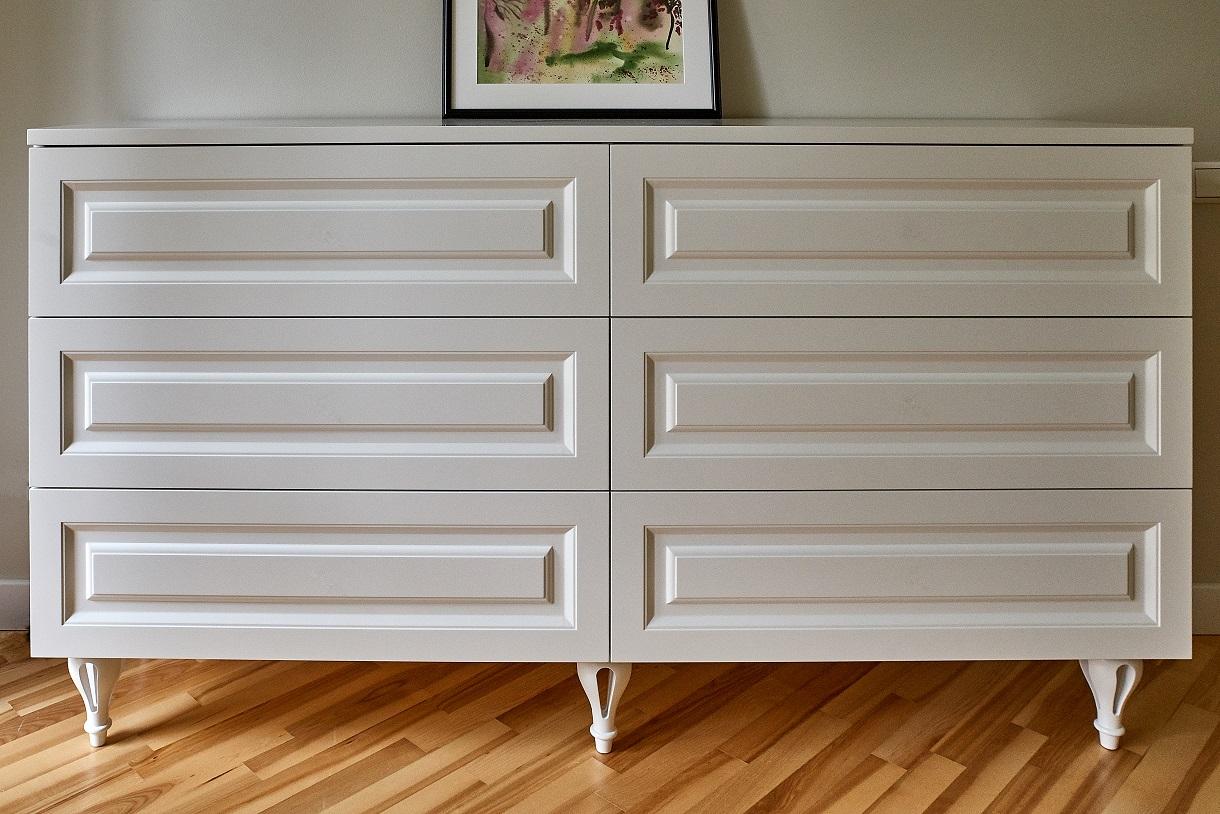 Komodą puošia klasikinio dizaino medinės kojelės ir frezuoti stalčių priekiai. Stalčiai be rankenėlių, jie atidaromi paspaudimu.