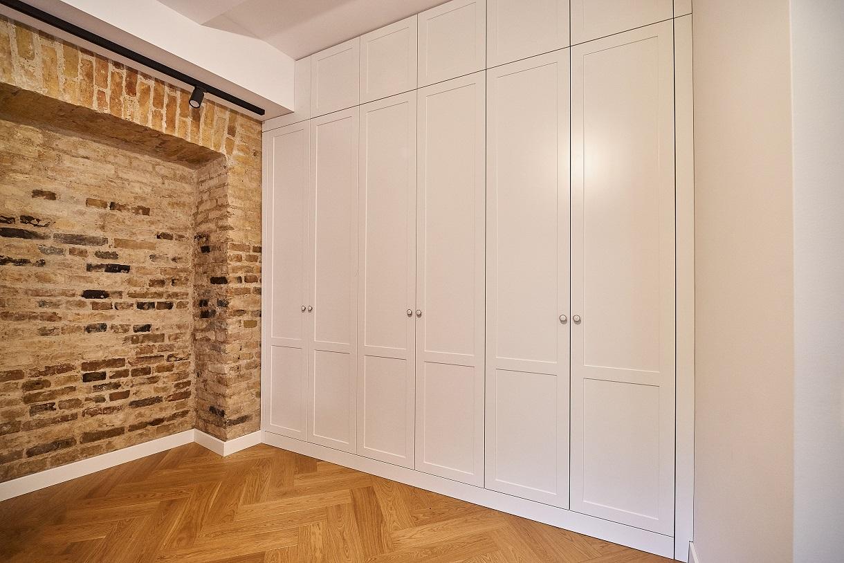 Apvalios klasikinės rankenėlės ir frezuoti filingai puošia baltas duris.