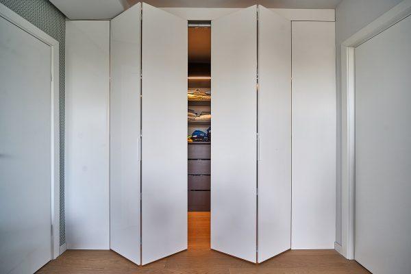 Minimali balta rankenėlė susilieja su durimis.