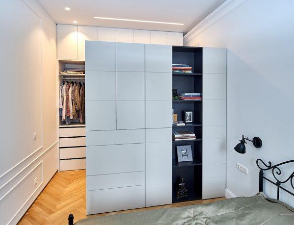 Patalpą skiria talpi spinta, kurios viena pusė skirta miegamajam, kita - drabužinei.