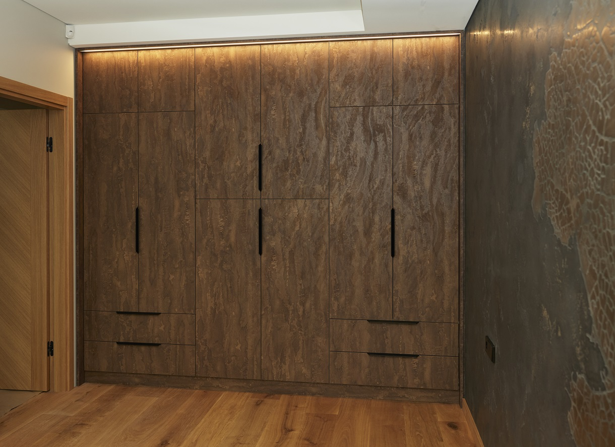 Rudas spintos ir sienos koloritas pabrėžia dizaino įdėją.