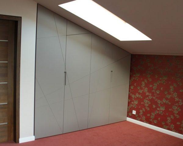 Šlaitinės spintos durys pagamintos iš MDF plokštės, matiškai pilkai dažytos ir dekoruotos linijiniu frezavimu.
